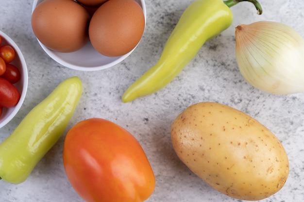 Patatas, tomates, pimientos, cebollas y huevos sobre cemento.
