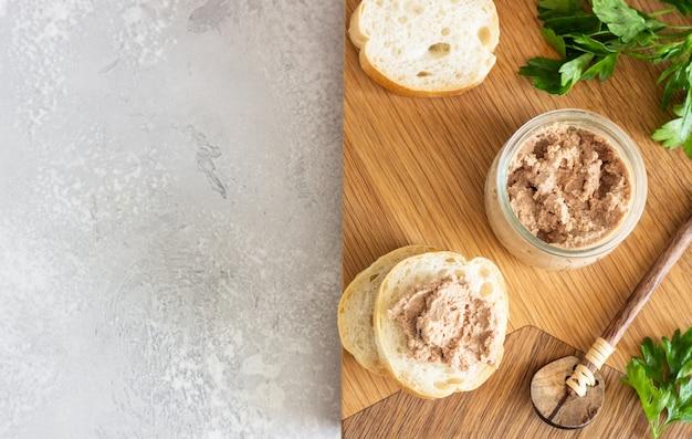 Paté de hígado en un frasco de vidrio con pan fresco y perejil sobre una tabla para cortar madera.