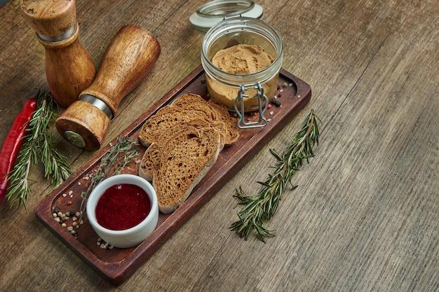 Paté de hígado de ganso casero fresco con pan de centeno y mermelada en bandeja de madera. vista cercana con espacio de copia