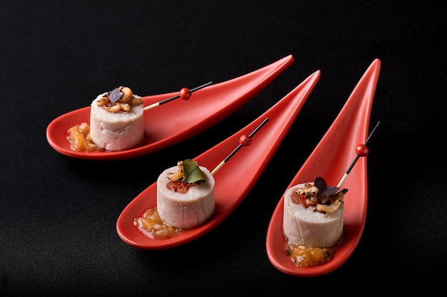 Paté de hígado de ganso, foie gras, servido sobre piedra negra en cucharas rojas japonesas. pasta servida con mermelada y nueces. concepto de comida fusión, bajo perfil, copia espacio.