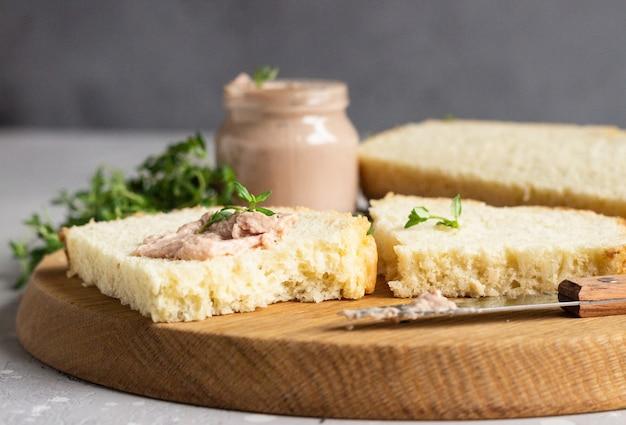 Paté de hígado de pollo casero fresco en pan con tomillo en una tabla para cortar madera.