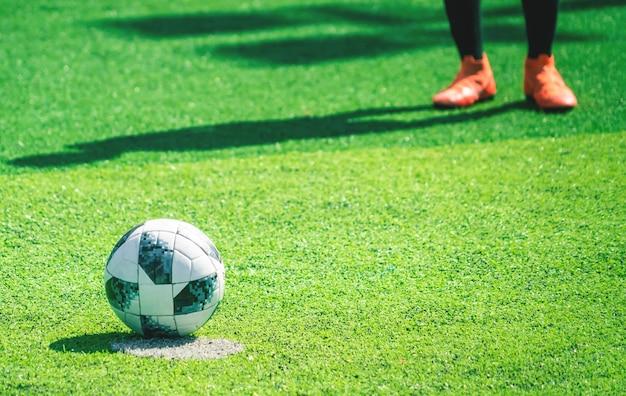 Patea el pie en la bota de fútbol parado en el campo de fútbol listo para patear el fútbol, para el concepto de entrenamiento de la academia de fútbol juvenil