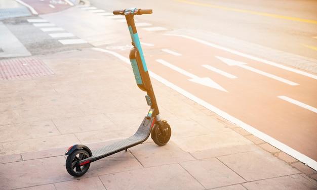Patear scooter en la acera cerca del carril bici