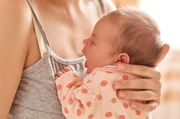 Paternidad y nueva vida, madre sin rostro con bebé recién nacido en brazos, mujer desconocida con camiseta gris sin mangas posando con su pequeño niño, niño bostezando.