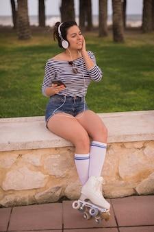 Un patinador femenino escuchando música en auriculares