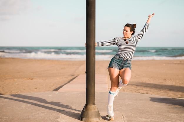 Patinador femenino joven de moda que sostiene el pilar que baila en la playa