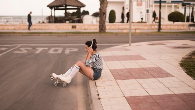 Patinador femenino joven que se sienta en música que escucha de la acera en el auricular