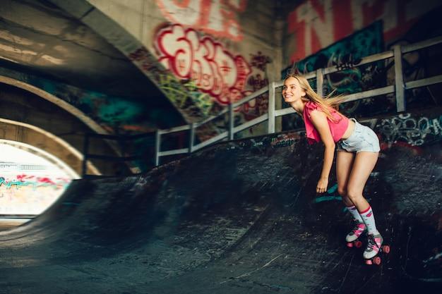 A este patinador le gusta hacer trucos arriesgados. ella está montando en rodillos. la chica está mirando hacia adelante. ella es feliz.