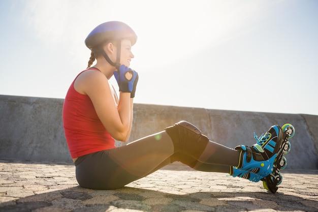 Patinador rubio deportivo sentado en el suelo y casco de sujeción