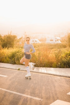 Patinador de sexo femenino joven sonriente que se coloca en una pierna que presenta en el camino
