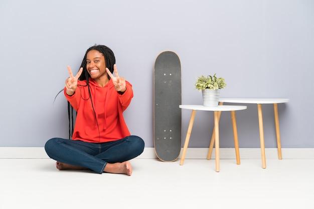 Patinadora afroamericana adolescente con cabello trenzado sentada en el suelo sonriendo y mostrando el signo de la victoria