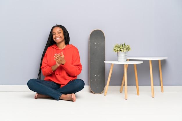 Patinadora afroamericana adolescente con cabello trenzado sentado en el suelo aplaudiendo
