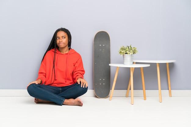 Patinadora afroamericana adolescente con cabello trenzado sentado en el suelo de pie y mirando hacia un lado