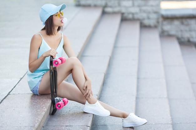 Patinadora. mujer joven atractiva al aire libre que sostiene el patín. hermosa mujer en verano.