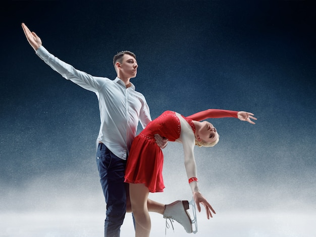 Patinadores artísticos profesionales de hombre y mujer que realizan espectáculo o competencia en la arena de hielo