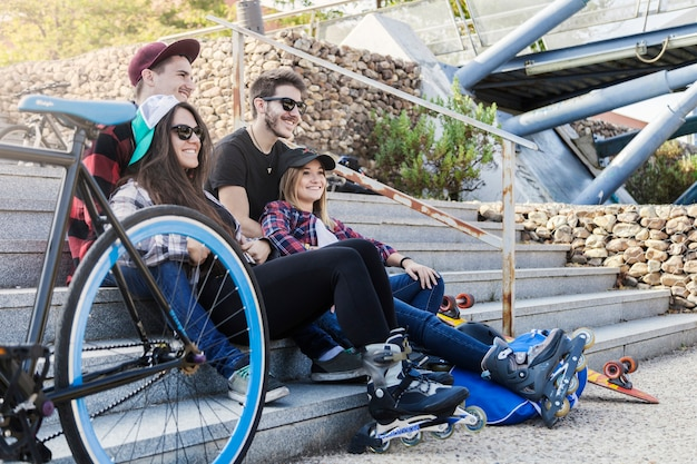 Patinadores descansando cerca de la bicicleta