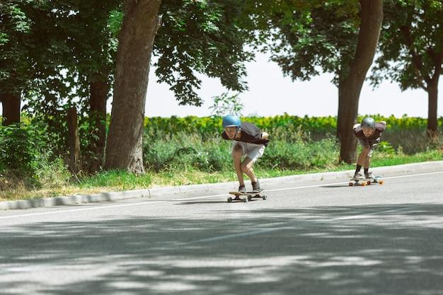 Patinadores haciendo un truco en la calle de la ciudad en un día soleado. hombres jóvenes en equipo de equitación y longboard cerca de la pradera en acción. concepto de actividad de ocio, deporte, extremo, afición y movimiento.