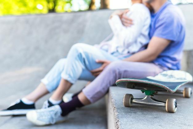 Patineta y gente joven. pareja de adolescentes en un skatepark durante su cita.