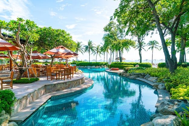 Patio al aire libre con silla y mesa alrededor de la piscina