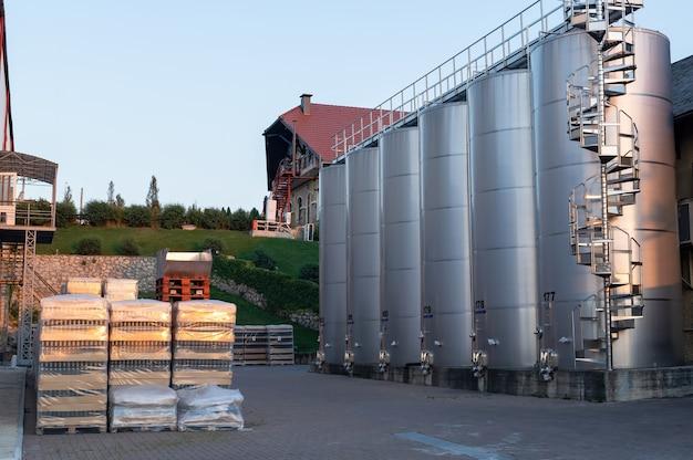 Patio de la bodega al atardecer con tanques de almacenamiento de vino de metal