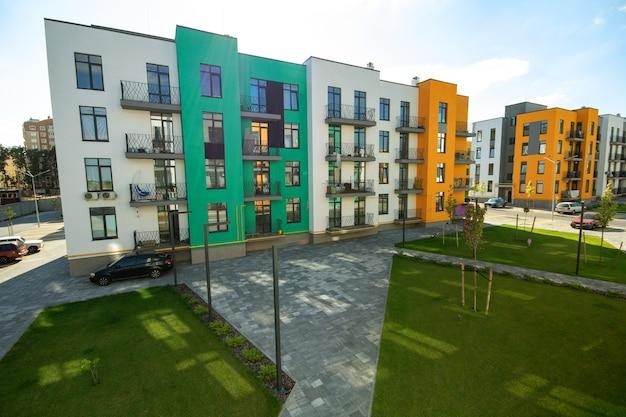 Patio entre edificios de apartamentos residenciales con césped verde y viviendas planas modernas. desarrollo inmobiliario.