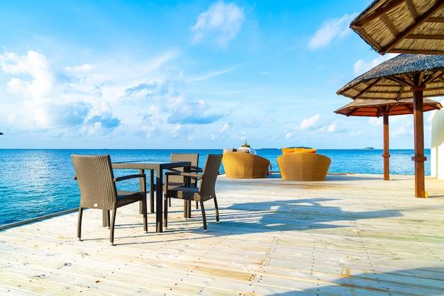 Patio exterior vacío cubierta y silla con océano azul en maldivas
