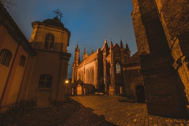 Patio de la iglesia católica del casco antiguo de santa ana vilna, un monumento de la arquitectura gótica de la ciudad de noche. lituania