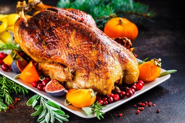 Pato al horno de navidad con hierbas y frutas en placa gris sobre fondo blanco.