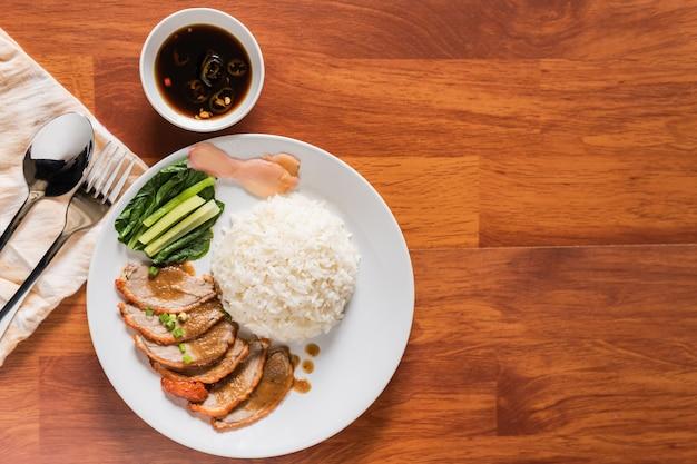 Pato asado con arroz con plato blanco en la vista superior de un escritorio de madera