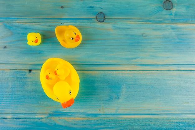 Pato de goma amarillo con patitos en escritorio turquesa
