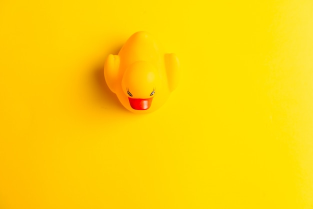 Pato de goma sobre fondo amarillo
