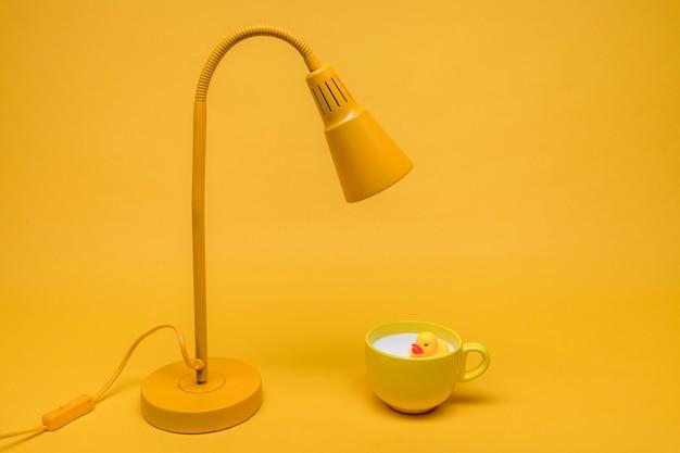 Pato de goma en taza de leche debajo de lámpara