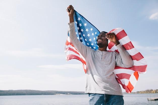 Patriota afroamericano feliz sosteniendo la bandera de estados unidos