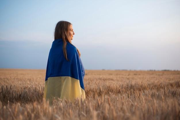 Patriótica chica rubia en campo de grano maduro en la noche