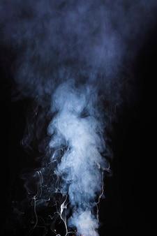 El patrón abstracto hecho de humo saliendo de un palo de incienso sobre fondo negro