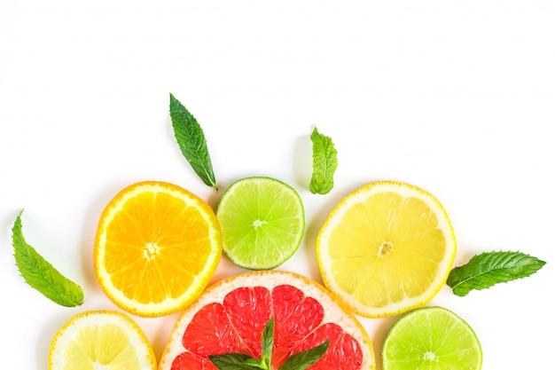 Patrón de alimentos cítricos sobre fondo blanco - frutas cítricas surtidas con hojas de menta