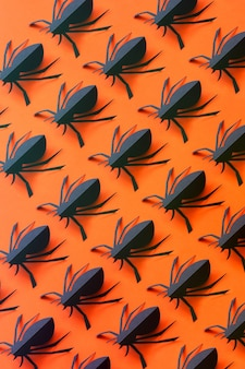 Patrón de arañas de papel sobre un fondo naranja