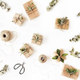 Patrón de arreglo creativo de cajas de artesanía y ramas verdes sobre fondo blanco.