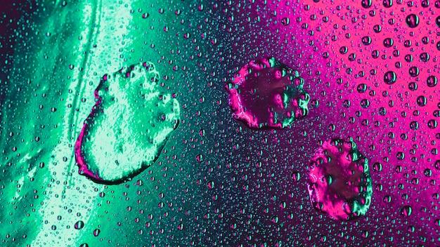 Patrón de burbujas sobre fondo de superficie verde y rosa mojado