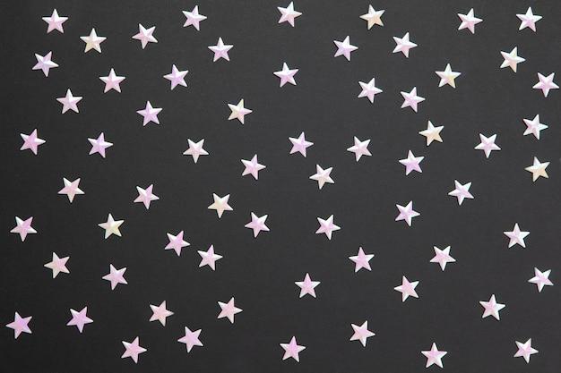 Patrón caótico de numerosos confeti de perlas en forma de pequeñas estrellas sobre fondo de papel negro. celebración, fiestas, rebajas, moda.