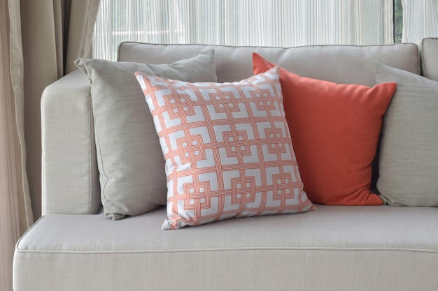 Patrón chino en naranja con almohadas de color naranja oscuro y gris en un sofá gris claro