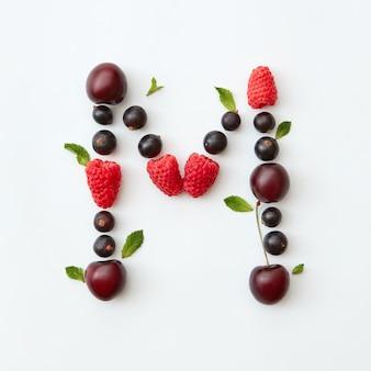 Patrón de colores de la letra m del alfabeto inglés de bayas maduras naturales - grosella negra, cerezas