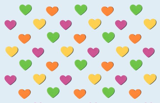 Patrón de colores transparente de corazones sobre fondo azul claro.