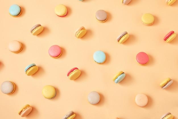 Un patrón de coloridos macarons de galletas francesas sobre fondo amarillo melocotón