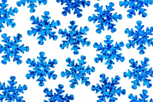 Patrón con copos de nieve decorativos azules sobre un fondo blanco.