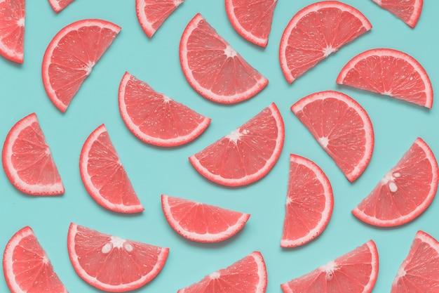 Patrón creativo de verano con rodajas de pomelo sobre fondo azul pastel