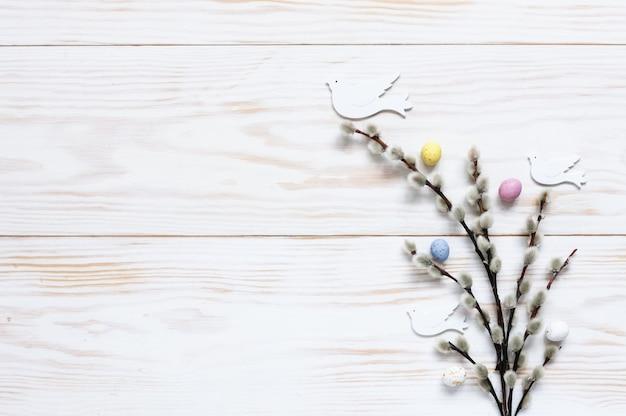 Patrón de decoración de pascua de coloridos huevos decorativos y figuras de paloma en las ramas de sauce.