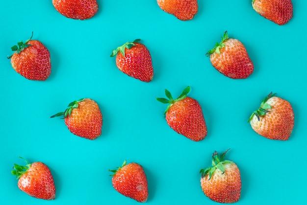 Patrón de deliciosas fresas sobre fondo azul