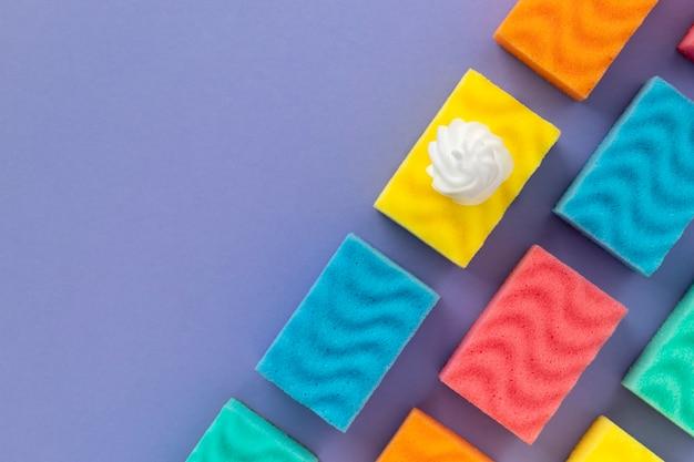 Patrón con esponjas de colores para lavar platos y espuma sobre fondo morado. concepto de servicio de limpieza