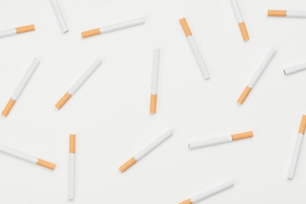 Patrón sin fisuras de cigarrillos sobre fondo blanco